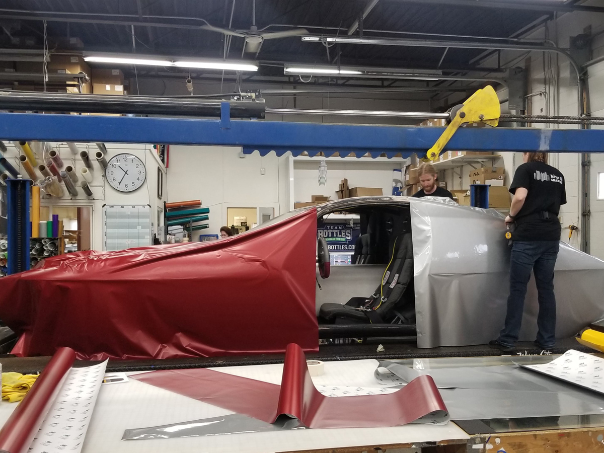 Vinyl draped over the Eos II as installers are working on wrapping the vehicle