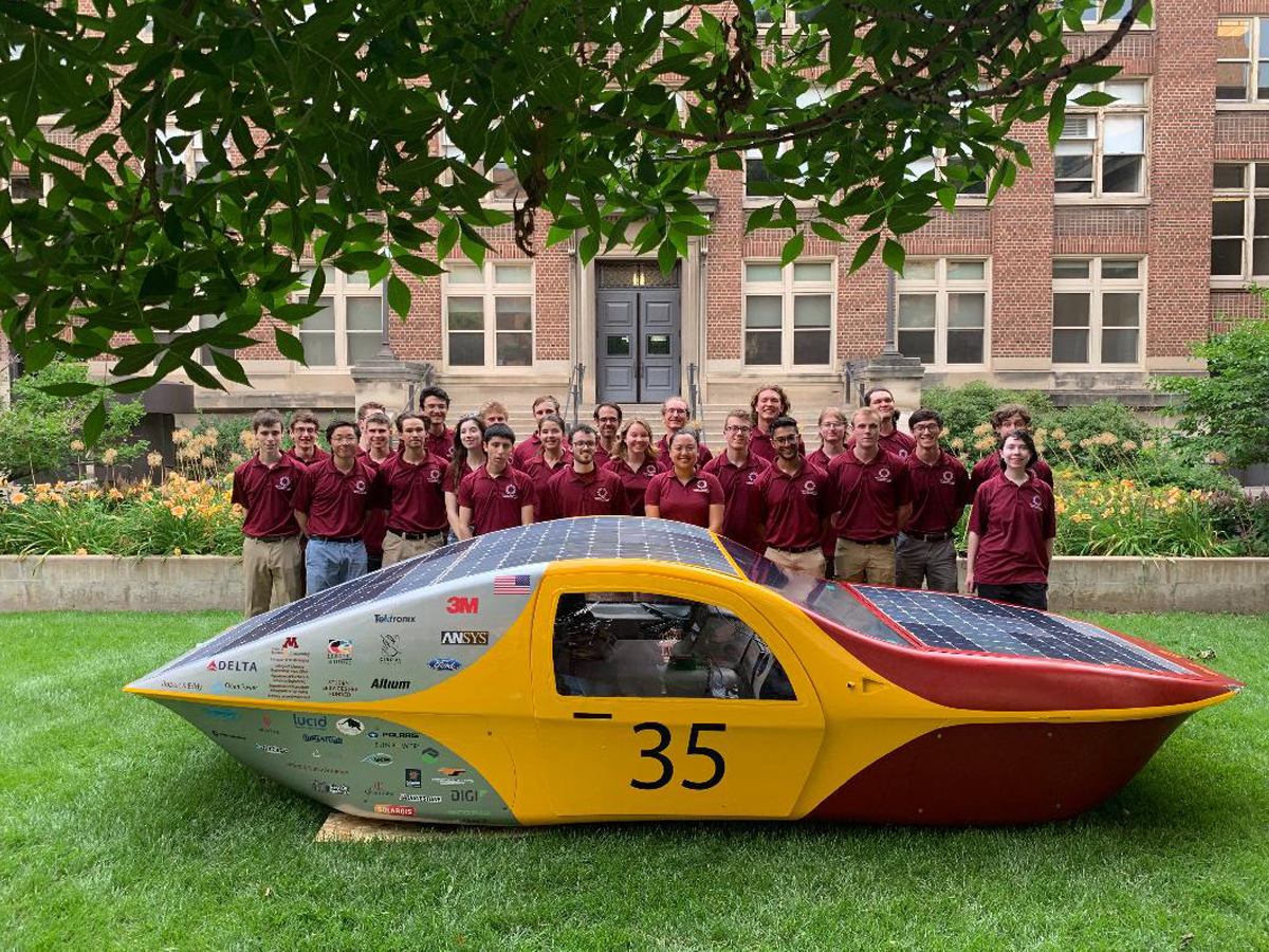 Students standing behind the Eos II solar vehicle